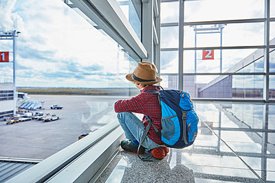 Boy sitting behind windowpane at the airport looking at airfield - p300m2069393 by Stefan Schütz
