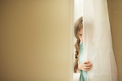 Shy Caucasian girl peeking around curtain - p555m1409052 by Shestock