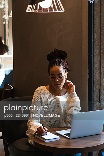 Beautiful young woman writing in diary while sitting with laptop at cafe - p300m2243981 by NOVELLIMAGE