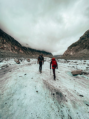 Two climbers hiking on glacier under cloudy sky - p1166m2212330 by Cavan Images
