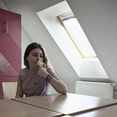 Junge Frau sitzt am Tisch und isst einen Apfel - p1383m1584333 von Wolfgang Steiner