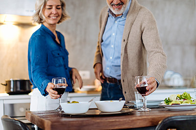 Mature couple raising wine glasses during dinner in kitchen at home - p300m2160338 by Sofie Delauw