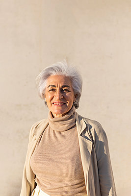 Smiling mature woman in front of wall during sunny day - p300m2281475 by PICUA ESTUDIO