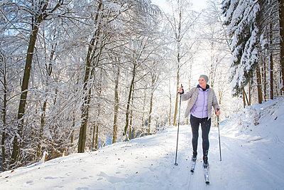 Frau auf Langlaufskiern im verschneitem Wald. - p948m2014776 von Sibylle Pietrek