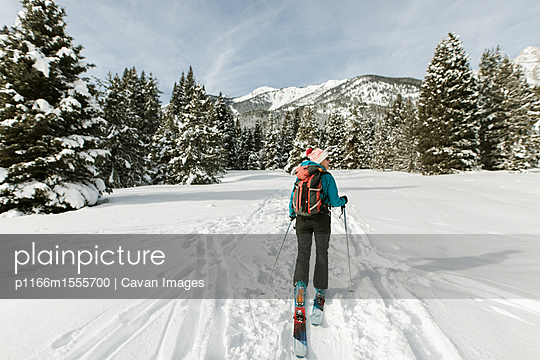 Rear view of woman with skies walking on snow covered field against sky - p1166m1555700 by Cavan Images