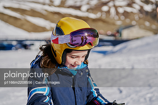 girl with helmet and glasses looks smiling on a ski slope - p1166m2208556 by Cavan Images