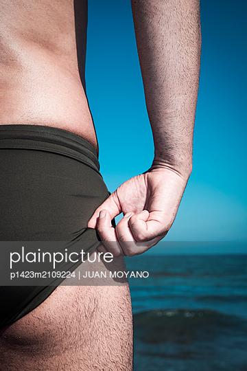 Man adjusting his swim briefs on the beach - p1423m2109224 von JUAN MOYANO
