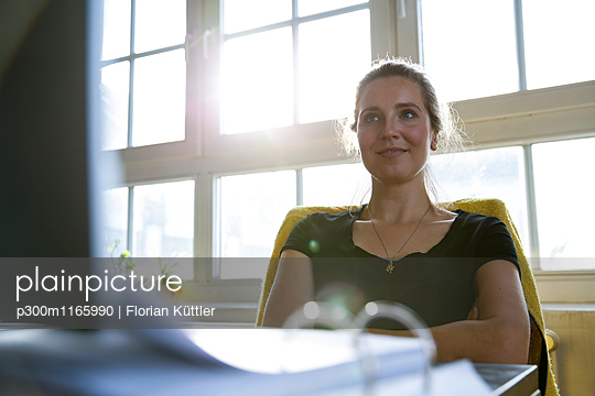 Woman sitting at desk with arms crossed - p300m1165990 by Florian Küttler