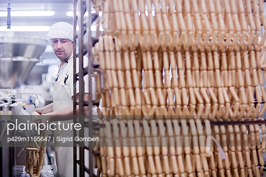 Factory worker making tofu sausages - p429m1155647 by Sigrid Gombert