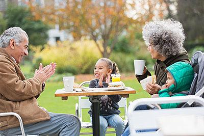 Grandparents and grandchildren enjoying lunch at park table - p1023m2161234 by Tom Merton