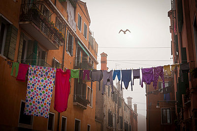 Clothes in a channel in Venice - p1281m1133542 by Lucie Jean