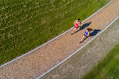Aerial view of female joggers on woodchip trail - p300m2005385 by Stefan Schurr