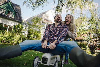 Laughing couple pretending to ride a toy car in the garden - p300m2167314 by Kniel Synnatzschke
