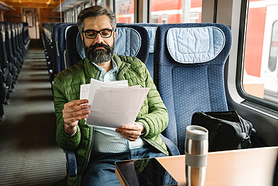 Man sitting in train reading documents - p300m2188132 by Hernandez and Sorokina