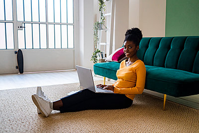 Smiling young Afro woman sitting with laptop on carpet against sofa in living room at home - p300m2251523 by Giorgio Fochesato