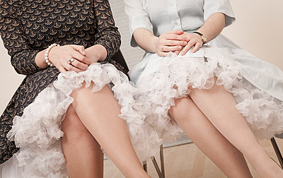 Young women in vintage dresses sitting side by side - p300m929812f by Dieter Schewig
