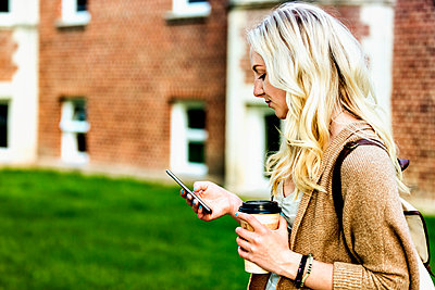A beautiful young woman with long blond hair holding a coffee cup and texting on her smart phone while walking in a university campus; Edmonton, Alberta, Canada - p442m2004143 by LJM Photo