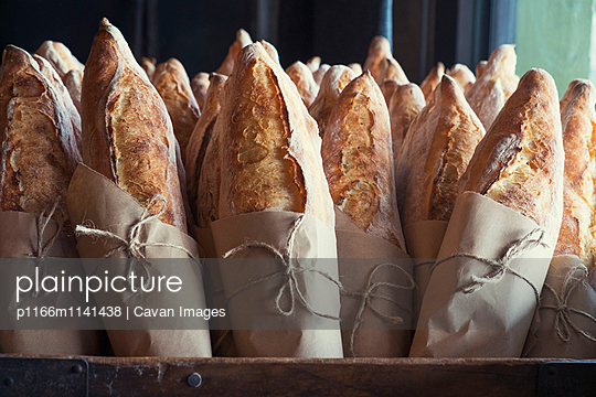 Fresh bread loafs displayed at bakery - p1166m1141438 by Cavan Images