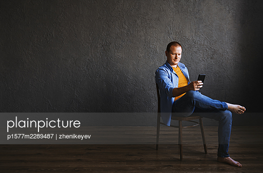 Redhead man sitting on the chair and using smartphone at his office - p1577m2289487 by zhenikeyev