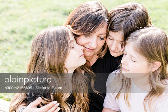 Happy mother with three triplet daughters on a meadow - p300m2156695 by Stefanie Baum