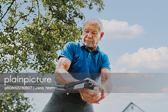 Elderly man performs sling training - p608m2230507 by Jens Nieth