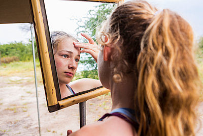Thirteen year old girl looking into mirror at a tented camp, applying sunscreen to her forehead - p1100m2214584 by Mint Images
