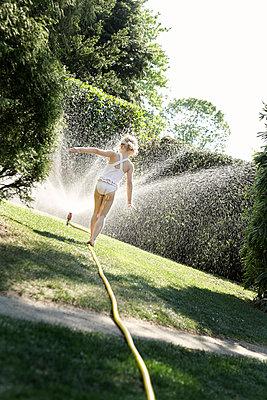 Mädchen balanciert auf Gartenschlauch - p1348m1215632 von HANDKE + NEU