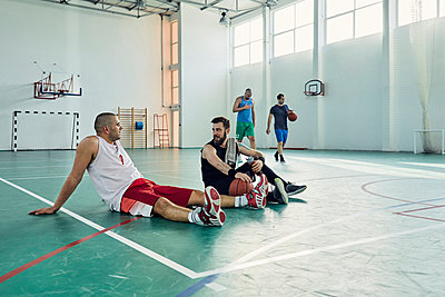 Basketball players during break, sitting on court - p300m1587301 by Zeljko Dangubic