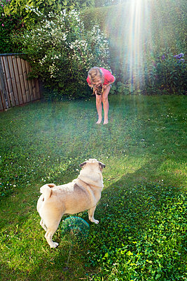Girl with dog in garden - p312m2052462 by Sara Winsnes