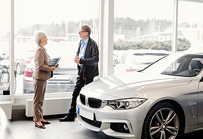 Side view of senior saleswoman discussing with man in car dealership store - p426m1036558f by Maskot