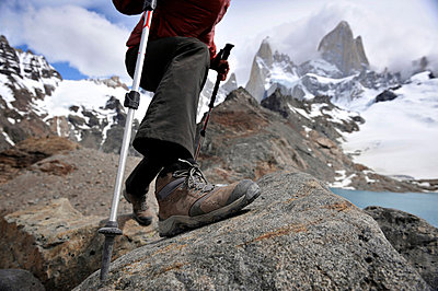 Woman takes a step with trekking poles at the Monte Fitz Roy Lookout in Los Glaciares National Park, El Chalten, Argentina - p924m734643 by HagePhoto