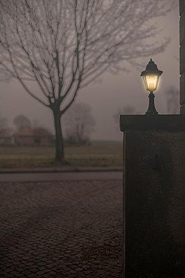 Beleuchtete Laterne in Hofeinfahrt - p946m956194 von Maren Becker