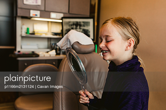 Young female dental patient happily examining her new braces smile - p1166m2131124 by Cavan Images