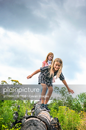 Two Young Girls Walking on Log - p1166m2207808 by Cavan Images