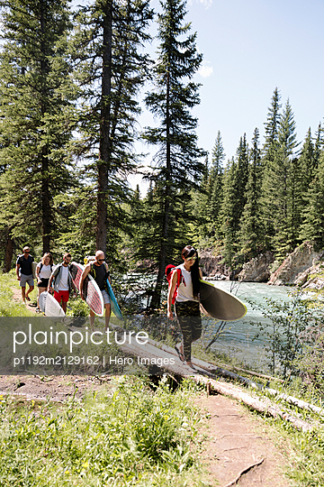 Surfer friends carrying surfboards along river in sunny woods - p1192m2129162 by Hero Images