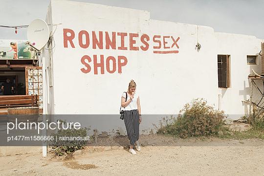 Junge Frau vor einem Sex-Shop in Südafrika - p1477m1586666 von rainandsalt