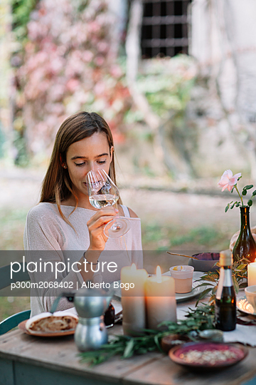 Woman tasting glass of wine at garden table - p300m2068402 by Alberto Bogo