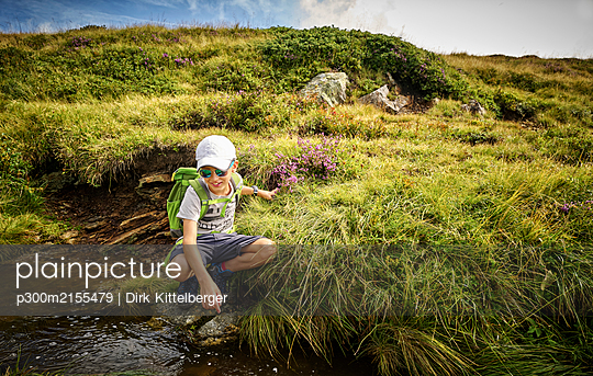 Boy crouching at a mountain stream, Passeier Valley, South Tyrol, Italy - p300m2155479 by Dirk Kittelberger