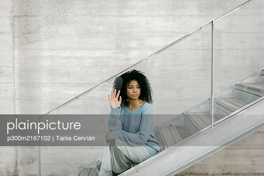 Beautiful young woman sitting on stairs behind a glass pane - p300m2167102 by Tania Cervián