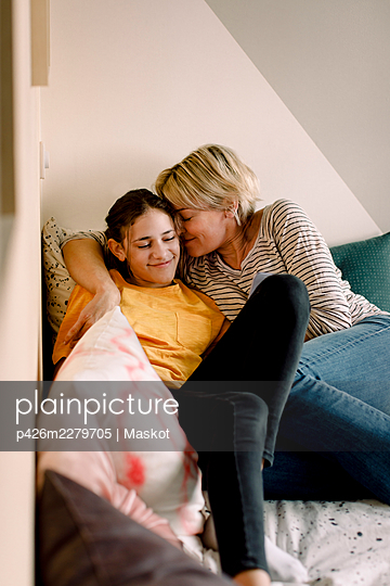 Smiling mother and daughter lying on bed at home - p426m2279705 by Maskot