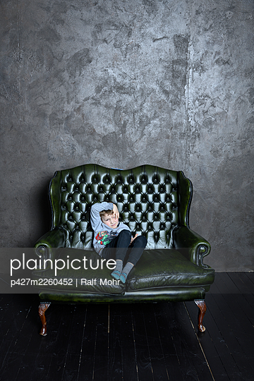 Little boy sitting on leather sofa - p427m2260452 by Ralf Mohr