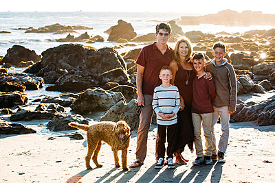 Portrait of happy family with dog standing at beach - p1166m1546850 by Cavan Images