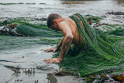 Man Covered in Seaweed - p1262m1125271 by Maryanne Gobble