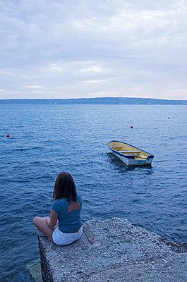 Frau sitzt am Meer - p1443m2039244 von SIMON SPITZNAGEL