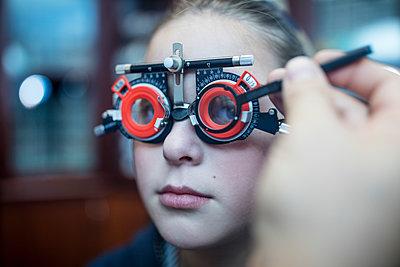 Girl doing eye test at optometrist - p300m1189638 by zerocreatives