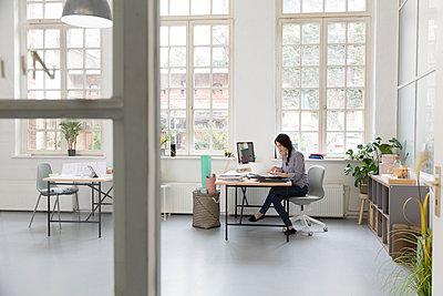 Woman working at desk in a loft office - p300m2012524 by Florian Küttler
