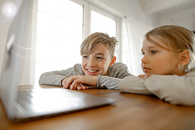 Happy brother and sister looking at laptop together at home - p300m2180303 by Katharina Mikhrin