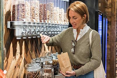 Smiling woman using food dispenser at supermarket - p300m2286808 by NOVELLIMAGE
