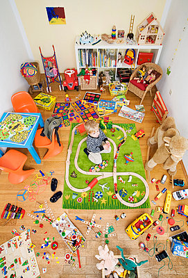 Boy plays in room crowded with toys - p4296236 by Lilian Henglein