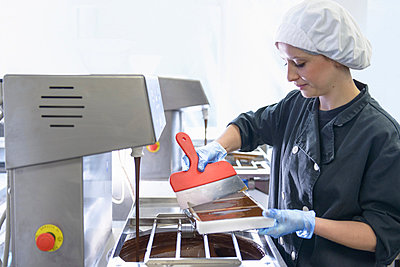 Chocolatier smoothing chocolate in moulds - p429m819887f by Monty Rakusen